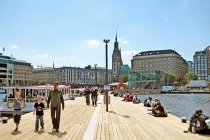 Hamburg, Germany - May 22, 2008: Pier of Lake Binnenalster - people relaxing - excursion boats starting from here for trips on the Alster. Historic town hall in the background